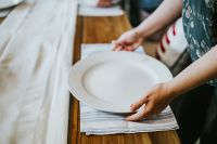 Kaboompics - Woman putting a plate on a table