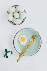 Easter flat lay with green eggs and fried egg on a plate