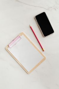 Kaboompics - Clipboard on a marble table, a mobile phone and a pencil, copy space