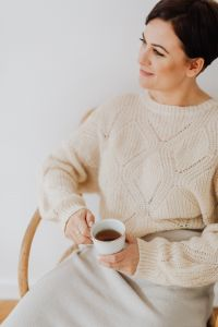 Kaboompics - A woman in a warm sweater drinks tea