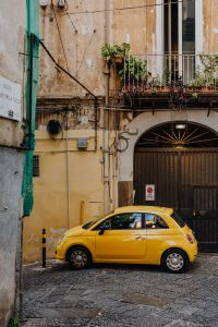 Yellow modern little car, Fiat 500, parked on a street in Naples