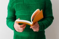 Kaboompics - A man in a green sweater reading a book, white background