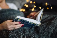 Kaboompics - Young woman at home reading Hygge book and drinking