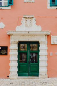 Pastel pink building with green doors and turquoise shutters, Rovinj, Croatia