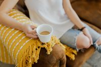 Kaboompics - Woman with a cup of coffee & book, yellow blanket, blue jeans pants