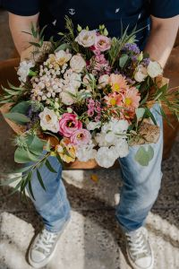 A man holds a beautiful bouquet of flowers