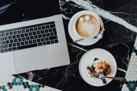 MacBook laptop, coffee and cake with meringue and whipped cream on black marble