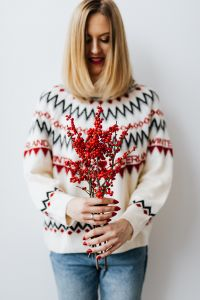 Woman in a white Christmas sweater holds rowanberry branch