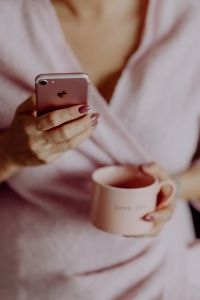 Kaboompics - A woman in a pink sweater holds a pink iPhone and a pink cup in her hands