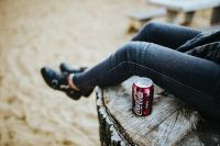 Kaboompics - Beautiful blonde woman relaxing with a can of coke on a tree stump by the beach