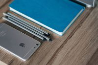 Kaboompics - Silver iPhone with a blue notebook and pencils