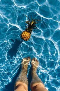 Kaboompics - Baby Pineapple & Women's Legs in a Swimming Pool