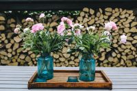 Pink flowers on a wooden table in a sunny garden