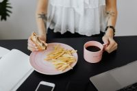 Businesswoman eats at work hamburger and fries, drink coffee