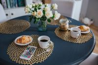 Round breakfast table with white flowers, golden mats, coffee, croissant and smartphone