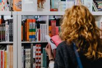 Kaboompics - Woman looking for a book in store