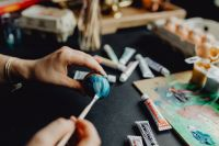Woman Painting Blue Easter Eggs