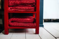 Kaboompics - Red woolen fabric stacked on a little red cupboard