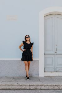 Kaboompics - A young woman with dark hair wearing a black dress poses by the blue building