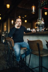 Kaboompics - Handsome young man with smartphone drinking whisky at bar or pub