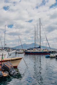 Boats moored in a marina in Naples, Vesuvius volcano in the background