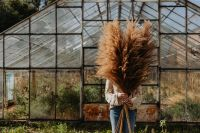 The woman is holding the pampas grass