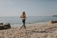 Woman jogging on the beach - running