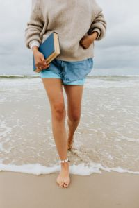 Kaboompics - A young woman with a book on the seashore