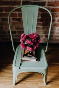 Kaboompics - Industrial pale green metal chair with a bouquet of pink flowers and books on it