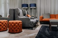 Pouf, cozy armchairs and sofa in living room