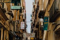 Narrow street with shop and restaurant signs in Naples
