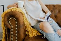 Woman with a cup of coffee & book, yellow blanket, blue jeans pants, brown couch
