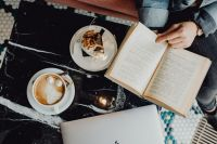 MacBook laptop, book, coffee and cake with meringue and whipped cream on black marble