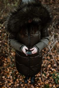 A woman wearing a green winter jacket with a furry hood uses a phone