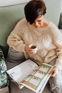 Kaboompics - The woman is drinking tea on the couch and reading the newspaper