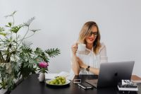 Kaboompics - A businesswoman drinks coffee and eats grapes at work