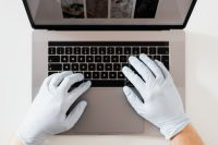 Kaboompics - Hands in hygienic glove typing on laptop