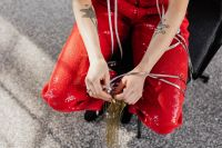 Kaboompics - Tattooed woman in red pants is sitting on a chair