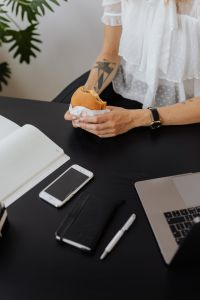 Kaboompics - A businesswoman eats a hamburger at work