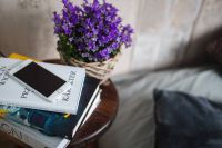 Books, purple flowers and a white smarphone on a wooden stool by the bed