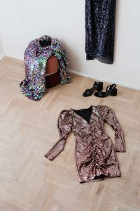 Kaboompics - colored sequin dresses and boots lie on a wooden parquet, blue dress hang on the white wall
