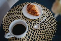 Coffee cup with a croissant on a golden mat