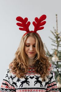 Kaboompics - The woman in the Christmas sweater and reindeer horns on her head