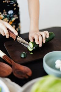 Teen Girl cuts cucumber