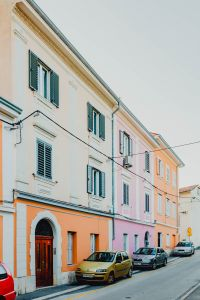 Colourful tenement houses in Izola, Slovenia. Cars parked on the street.