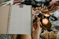 Kaboompics - Writing in a notebook lying in bed, with coffee, candles, and gingerbreads