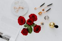 Kaboompics - Red roses, gold rings, perfume brushes and make-up accessories on white marble