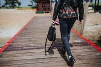 Woman with a black bag and a can of coke walking on a wooden pier