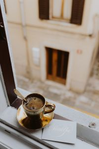Kaboompics - Drink coffee in a golden cup at the window