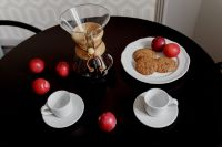 Breakfast served with coffee, cookies and plums